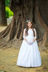 First Communion beautiful girl. Portrait of cute little girl on white dress and wreath on first holy communion