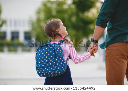 first day at school. father leads a little child school girl in first grade #1155424492