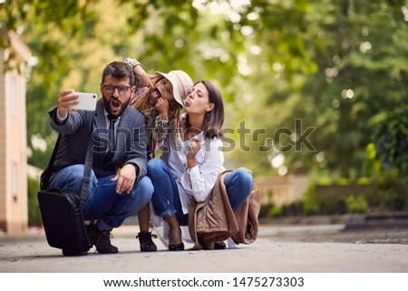 first day at school, silly parents and girl making a photo in front of school