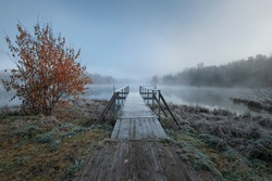 First frost on a forest misty lake with a pier, autumn landscape