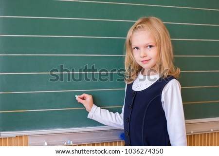 First grade pupil a girl writing on green blackboard at school lesson #1036274350