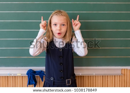 First grade pupil a girl writing on green blackboard at school lesson #1038178849