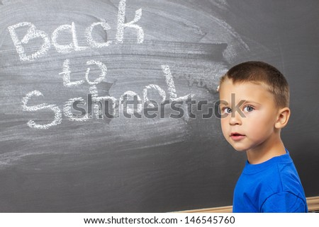 first grade student  writing  on chalkboard in classroom
