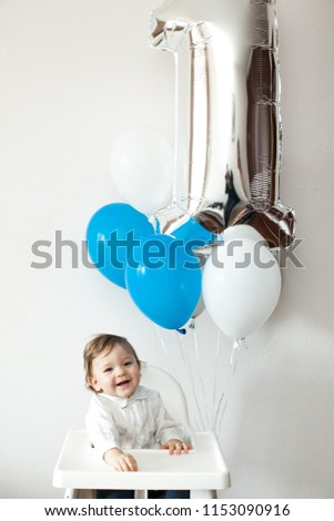 First Happy birthday. Child in the day of birth one year. Curious baby boy poking in his first birthday cake ストックフォト ©
