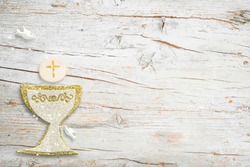 First Holy Communion invitations, silver and gold chalice and dove on white wooden background with empty space for text and photos