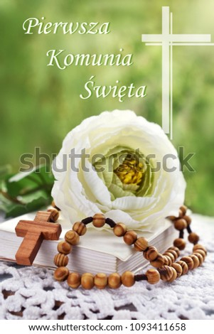 First Holy Communion still life with wooden rosary lying on prayer book , white flower and polish text (First Holy Communion) #1093411658