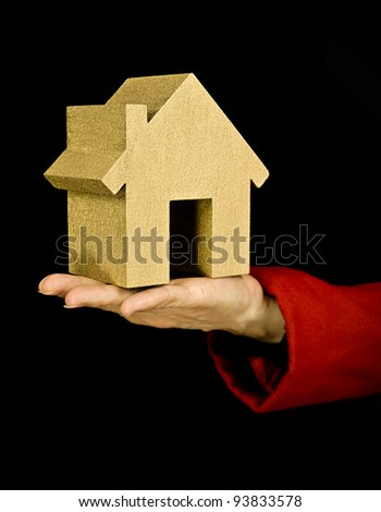 first house, woman holding golden house to show property purchase