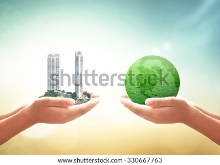 First, human hand holding the city. Second, human hand holding a green earth of grass  over blurred nature background. Ecological City, World Environment Day concept.