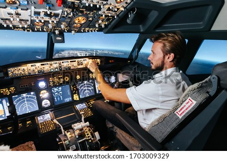 First officer is controlling autopilot and parameters for safety flight. Cockpit of Boeing aircraft. Content is good any airline. Сток-фото ©