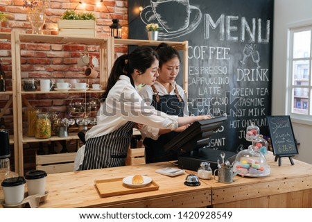 first part time job in summer concept. professional barista teaching young girl new employee how to using tablet to take customer order in cafe bar counter in coffee shop. coworkers help each other #1420928549