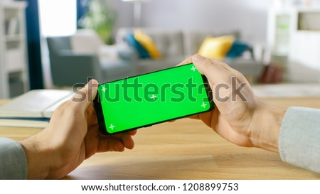 First Person Close-up of the Man Holding Green Screen Smartphone in Landscape Mode and Playing in a Racing Video Game by Tilting Mobile Phone. Background Cozy Living Room.