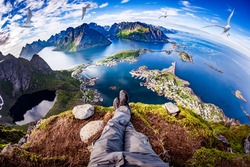 First person perspective shot from a hiker sitting at the edge of a cliff at Lofoten is an archipelago in the county of Nordland, Norway. Fisheye lens.