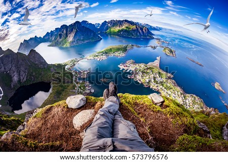 Photo of  First person perspective shot from a hiker sitting at the edge of a cliff at Lofoten is an archipelago in the county of Nordland, Norway. Fisheye lens.