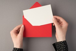 First person top view photo of female hands holding open red envelope with white card on isolated grey background with copyspace