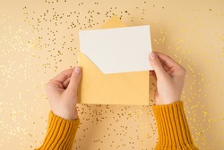 First person top view photo of female hands in yellow pullover holding open pastel yellow envelope with white card over scattered golden sequins on isolated pastel orange background with blank space