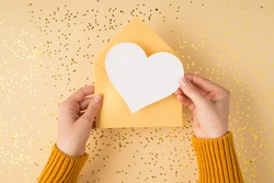 First person top view photo of female hands in yellow sweater holding open pastel yellow envelope with white paper heart over scattered golden sequins isolated light orange background with copyspace