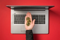 First person top view photo of outstretched hand demonstrating three gold coins with bitcoin symbol over open grey laptop on isolated red background
