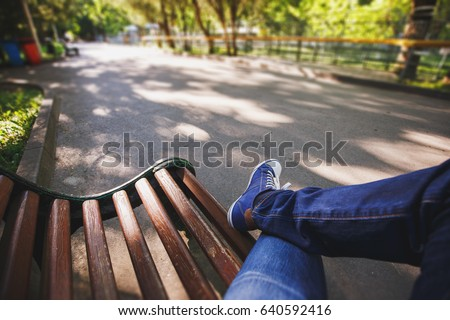 Photo of  First-person view a man sitting on wooden bench in the park.