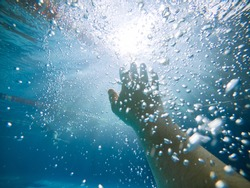first person view. drowning man under water. air bubbles. hand