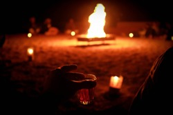 First person view: man holding glass of herbal tea in his hand, fireplace in front of him, blured bedouin silhouettes in the background. Late night, Wadi Rum desert, Jordan.