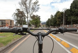 First person view of a handle bars and setam bicycle over a bike path in middle of a city with blue cloudy sky and trees at background