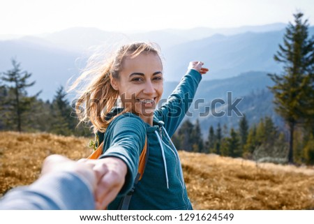 first person view of a happy attractive woman hiker standing on edge of mountain ridge against background of sunset. Woman is holding someone hand and greeting a sunset. Traveling and follow me