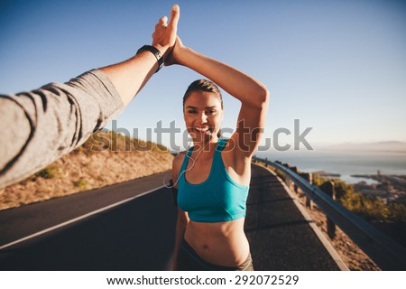 Photo of  First person view of a man and woman high fiving. Happy young woman giving high five to man after outdoor training. Couple of runner on country road looking happy.