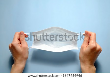 First person view of a woman holding face mask over blue textured table background. Protective raspiratory mask for spreading virus. Close up, copy space, top view, flat lay.