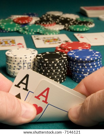 First person view of pocket aces in a game of Texas Hold-em with a full house showing on the board