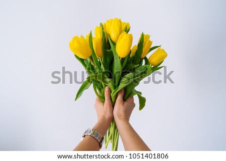 first person view. woman hold bouquet of yellow tulips. white background