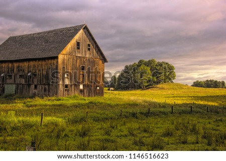First rays of light. Early summer morning as the sun lights up the morning sky and the old barn in Bath NH. USA