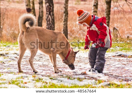 First snow. Little boy playing with his dog.