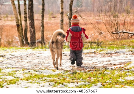 First snow. Little boy walking with his dog.
