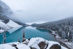 First snow, Morning at Moraine Lake in Banff National Park Alberta Canada Snow-covered winter mountain lake in a winter atmosphere. Beautiful nature background photo. Landscape in the misty weather.