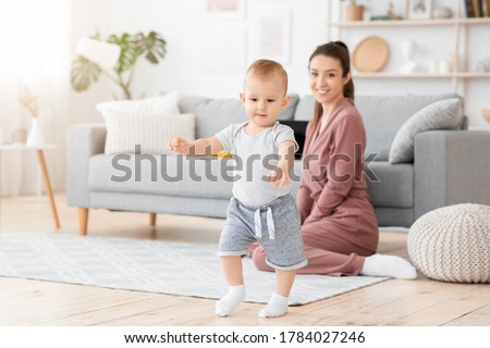 First Steps. Adorable smiling baby boy learning how to walk at home, happy mom proud of her little child sitting on background, copy space