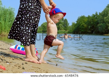 First steps into water - mother plays with cute baby boy on beach. Shot in July, Dniepropetrovsk, Ukraine.