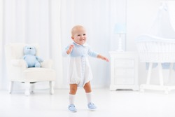 First steps of baby boy learning to walk in white sunny bedroom with bassinet, rocking chair, play mat and toy bear. Footwear for young children. Right shoes for little kids feet. Nursery interior