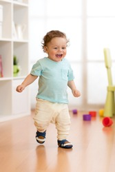 First steps of baby toddler learning to walk in living room. Footwear for little children.