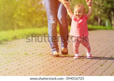 first steps of little girl in summer park