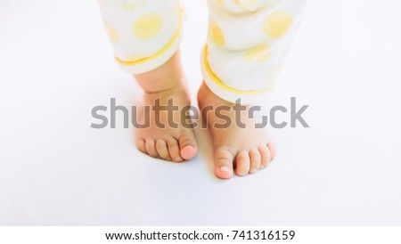 first steps of new born baby, feet of toddler on the white floor.