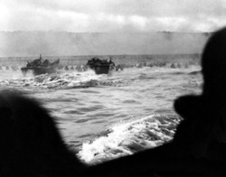 First wave of U.S. invasion troops approach Omaha beach during the D-Day invasion of Normandy. Smoke screen in the distance and soldiers advance under fire with water up to the waist. June 6, 1944