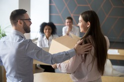 First working day in office concept, friendly male boss welcoming new female employee holding box with belongings, company executive introducing supporting hired team member starting work, rear view