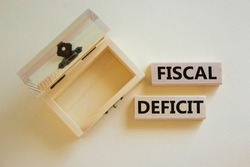 Fiscal deficit symbol. Concept words 'fiscal deficit' on blocks on a beautiful white background, small empthy chest. Business and fiscal deficit concept, copy space.