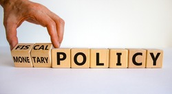 Fiscal or monetary policy symbol. Hand turns cubes and changes words 'fiscal policy' to 'monetary policy'. Beautiful white background. Business and fiscal or monetary policy concept. Copy space.