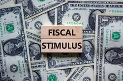 Fiscal stimulus symbol. Concept words 'fiscal stimulus' on wooden blocks on a beautiful background from dollar bills. Business and fiscal stimulus concept.