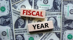 Fiscal year symbol. Concept words 'fiscal year' on wooden blocks on a beautiful background from dollar bills. Business and fiscal year concept.