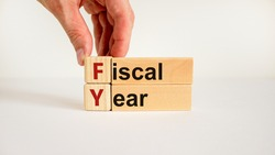Fiscal year symbol. Concept words 'fiscal year' on wooden cubes and blocks on a beautiful white background. Businessman hand. Business and fiscal year concept.