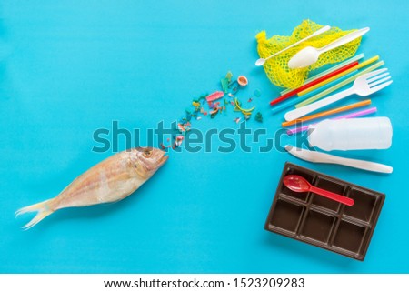Fish about to consume micro plastics breaking from plastic trash in the sea. Flat lay on blue background. Pollution concept.