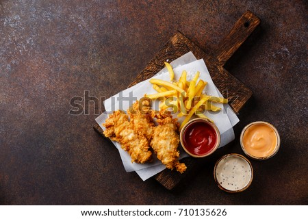 Fish and Chips british fast food with three popular sauce for choice on brown background copy space