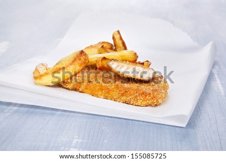 Fish and chips on blue wooden background. Delicious seafood background.